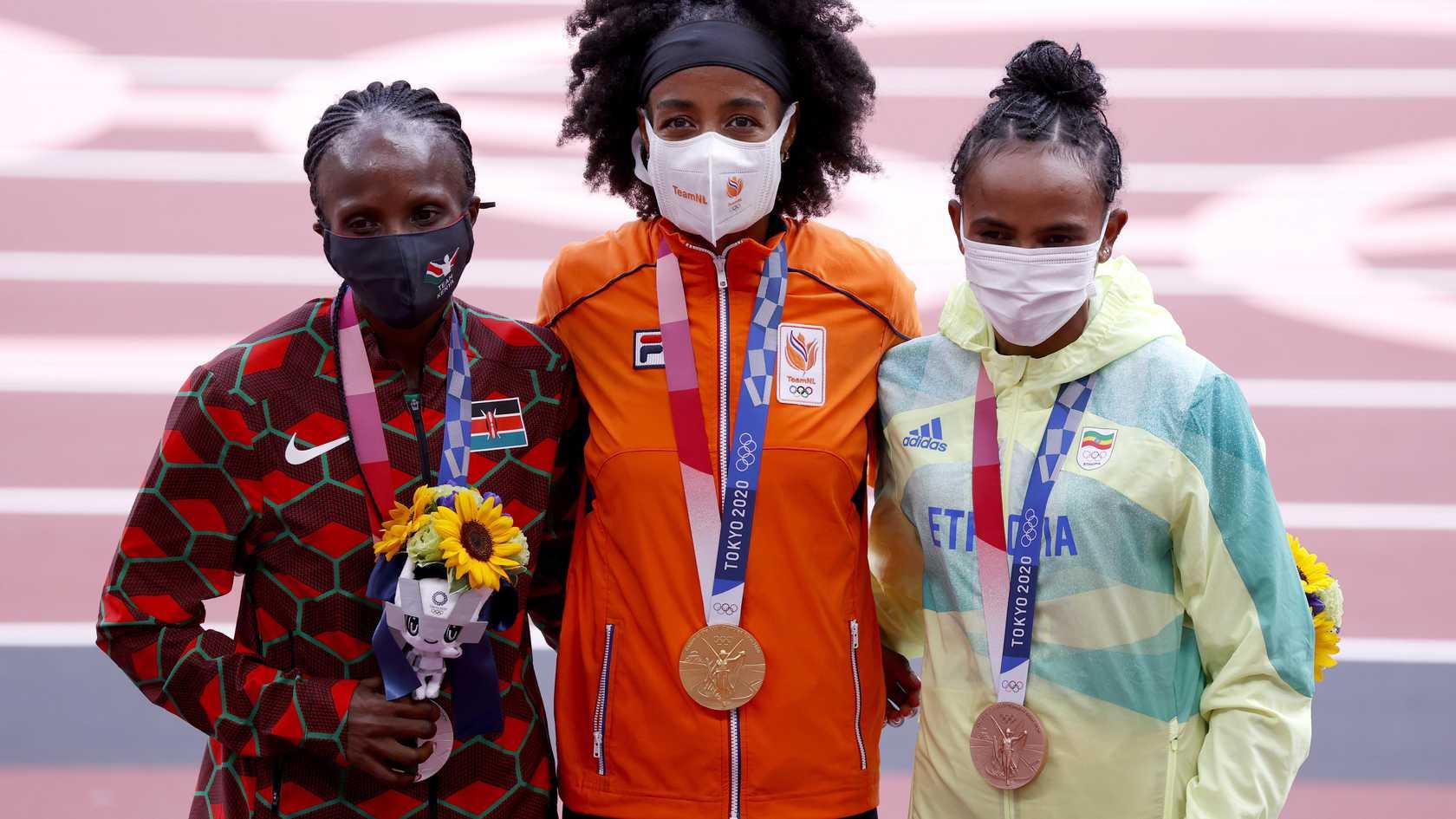 Sifan Hassan (tengah) menerima medali emas pertama dari tiga medali emas yang ia cita-citakan di Tokyo 2020.