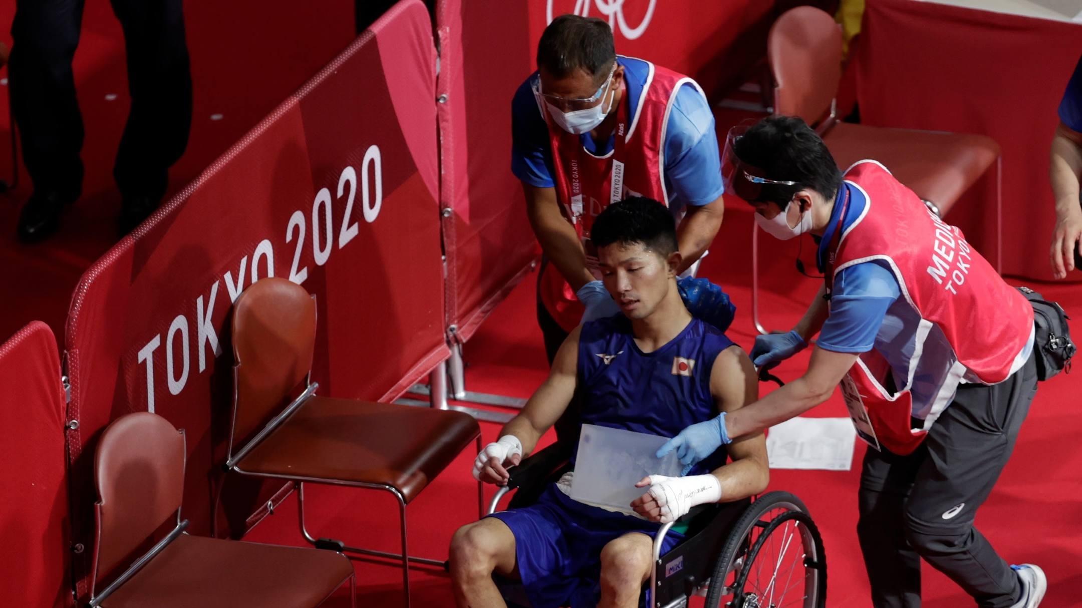 Tanaka harus menggunakan kursi roda untuk meninggalkan area kompetisi.  Foto: Reuters