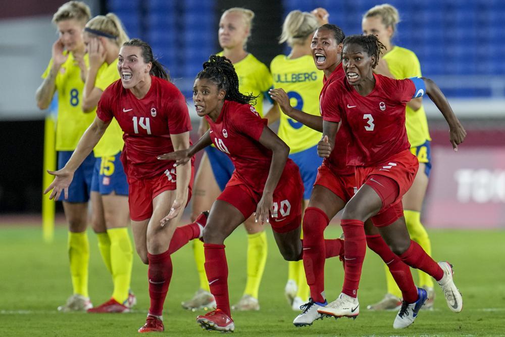 Các cầu thủ Canada phấn khích sau khi thắng Thuỵ Điển ở loạt luân lưu chung kết bóng đá nữ Olympic Tokyo 2002 trên sân Yokohama tối 6/8. Ảnh: AP