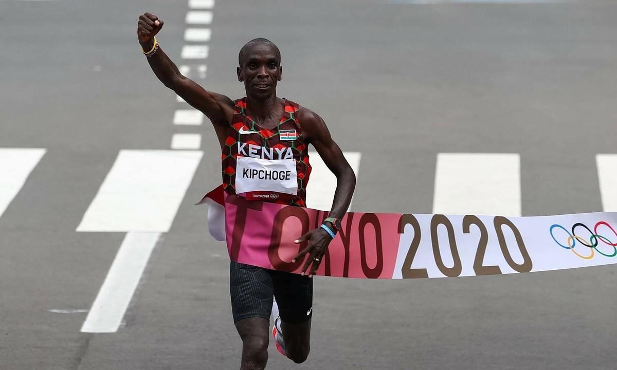 Kipchoge ăn mừng khi cán đích đầu tiên ở nội dung full marathon sáng 8/8. Ảnh: AFP.