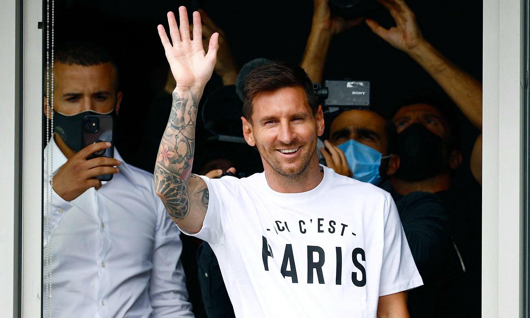Messi โบกมือให้แฟน PSG จากสนามบิน Le Bourget  บนเสื้อของเขามีข้อความจารึกว่า ici çest Paris ซึ่งแปลว่า นี่คือปารีส  ภาพ: Twitter/Reshad Rahman