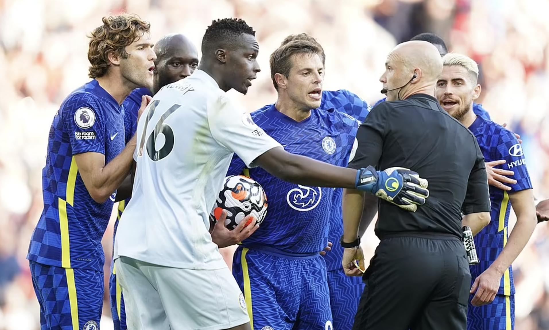 Cầu thủ Chelsea bủa vây trọng tài Anthony Taylor để tranh cãi về phạt đền và thẻ đỏ. Ảnh: PA