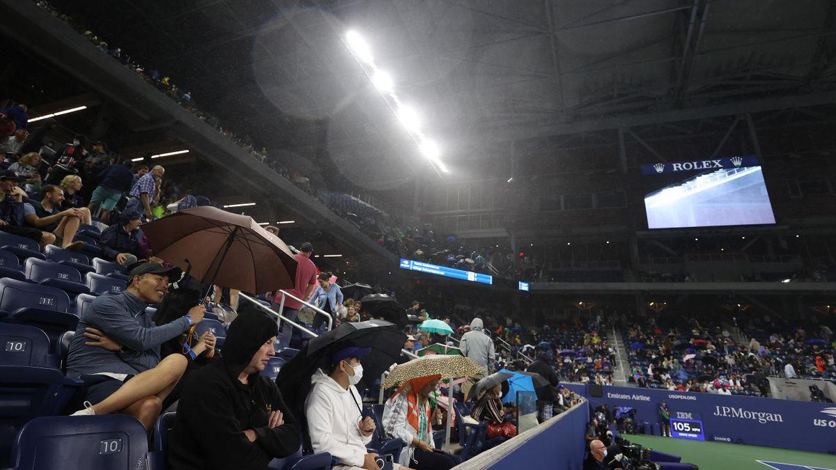Khán giả phải che ô khi ngồi trong sân có mái che, trước khi trận đấu bị hoãn. Ảnh: USA Today