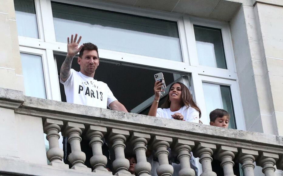 Messi và vợ con vẫy chào người hâm mộ từ ban công phòng khách sạn Le Royal Monceau. Ảnh: Le Parisien