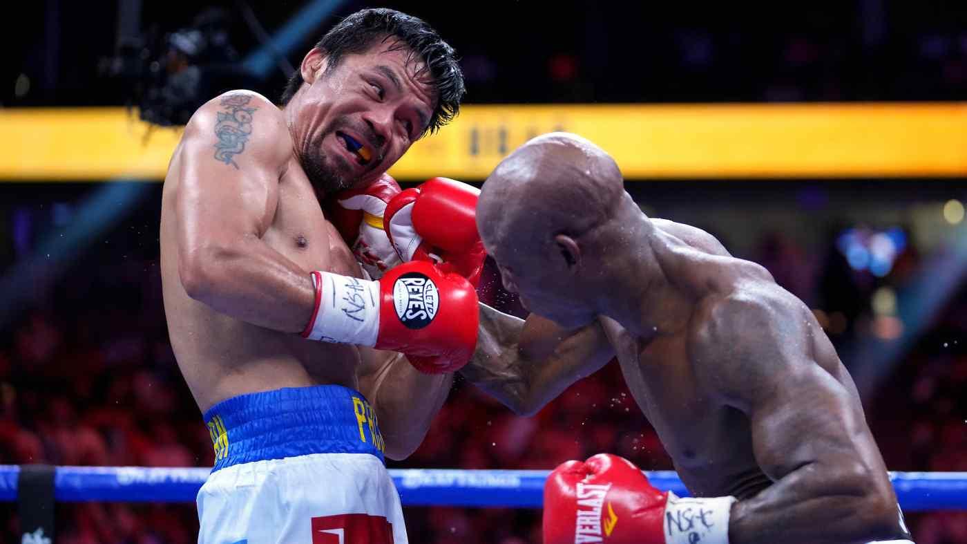 Pacquiao (trái) trong trận đấu cuối cùng của sự nghiệp, gặp Yordenis Ugas tại Las Vegas tối 21/8 (Mỹ). Ảnh: Reuters