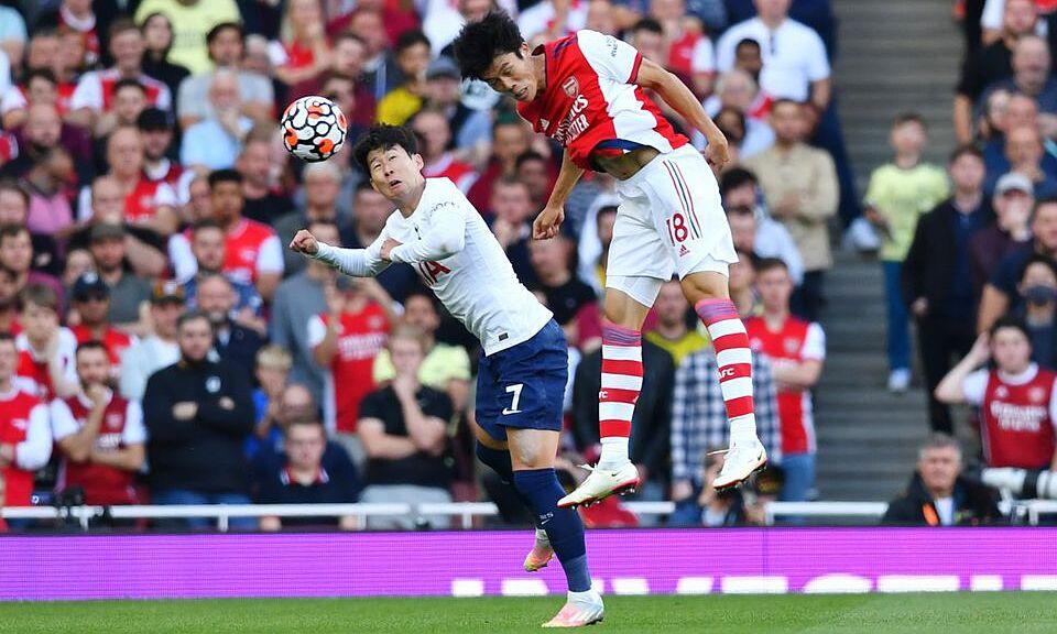 Tomiyasu (phải) tranh chấp bóng bổng với Son Heung-min ở derby Bắc London hôm 26/9. Ảnh: Reuters