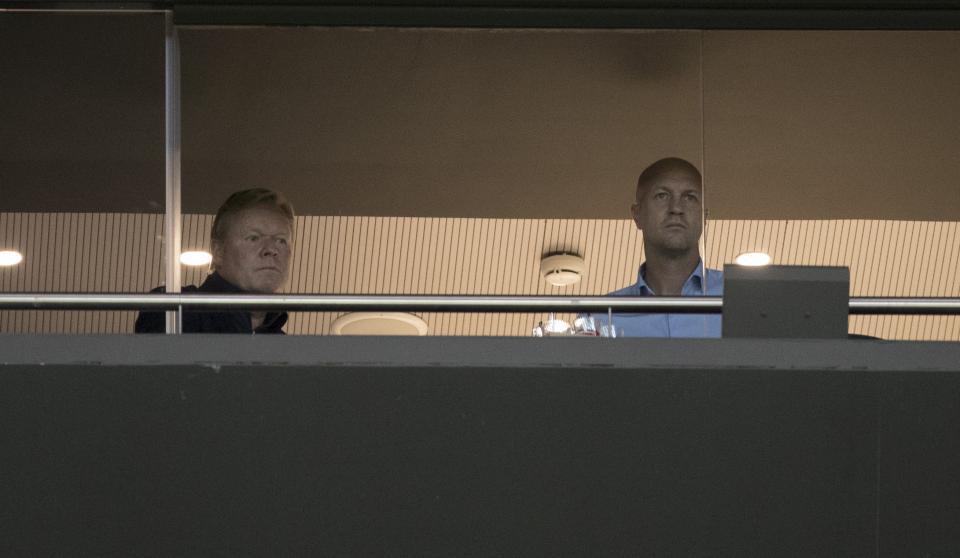 Koeman (trái) thẫn thờ khi xem trận đấu từ khán đài cạnh Jordi Cruyff hôm 2/10. Ông bị cấm chỉ đạo trận này vì thẻ đỏ nhận trong trận hoà Cadiz 0-0 hôm 24/9. Ảnh: Propias