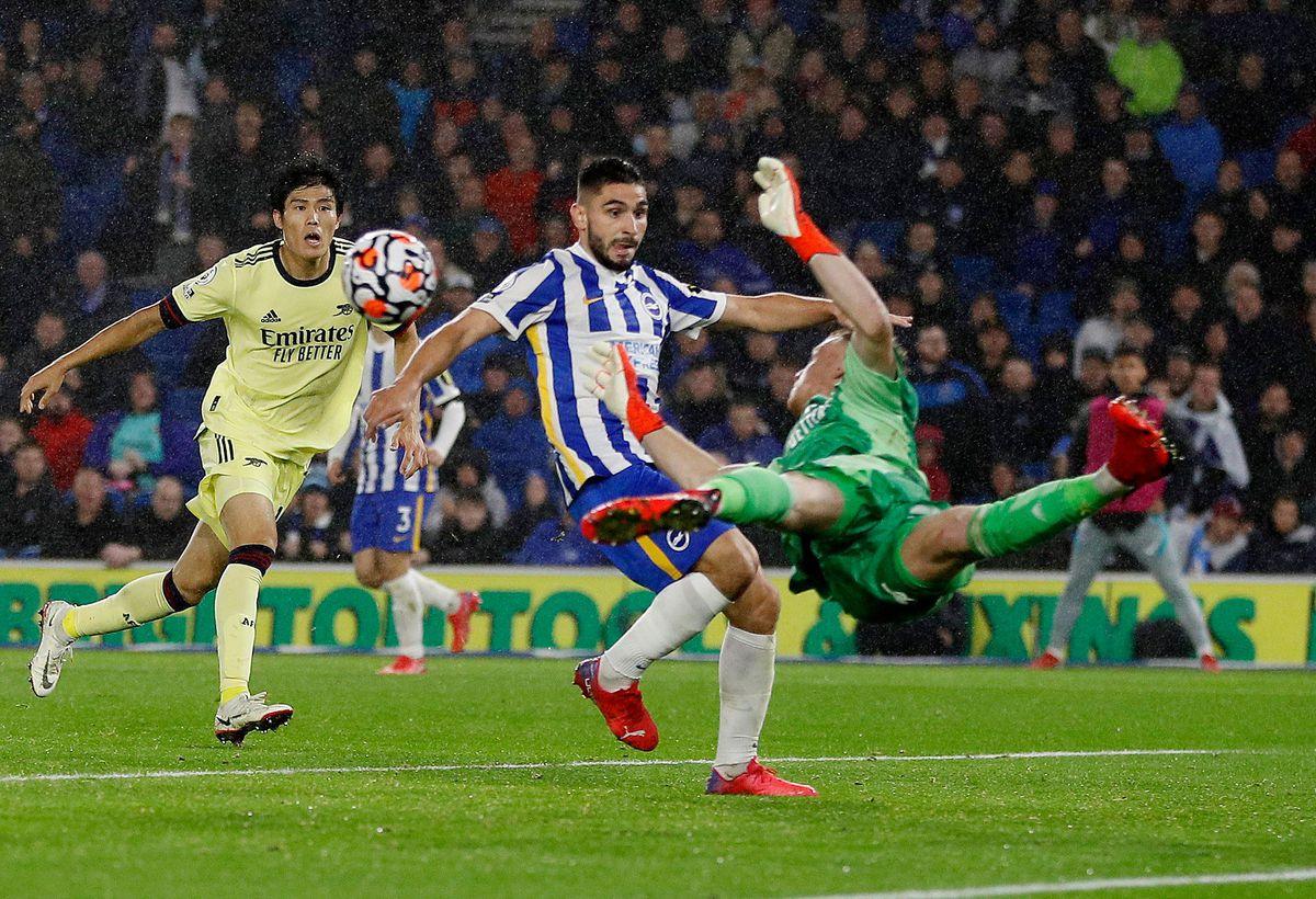 Thủ môn Ramsdale bay người cản bóng trước chân Neal Maupay sau khi tiền đạo Brighton vượt qua Tomiyasu trong trận đấu tại sân American Express hôm 2/10. Ảnh: Reuters