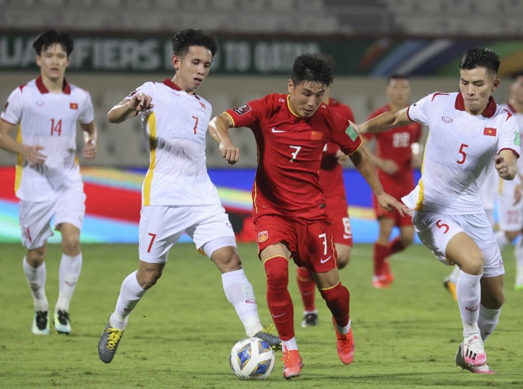 Hậu vệ Nguyễn Phong Hồng Duy (trái) và Nguyễn Thanh Bình (phải) truy cản tiền đạo Trung Quốc Wu Lei ở vòng loại World Cup 2022 trên sân Sharjah. Ảnh: AFP