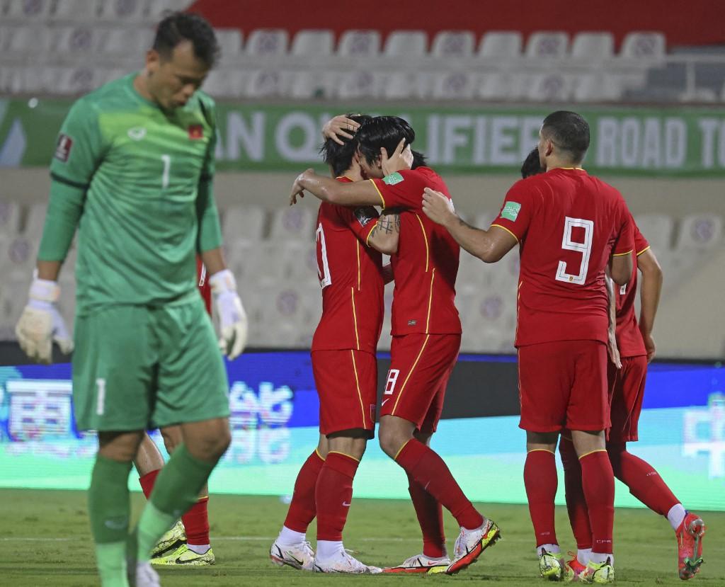 Thủ môn Tấn Trường buồn bã, trong khi các cầu thủ Trung Quốc ăn mừng ba điểm đầu tiên. Ảnh: AFP