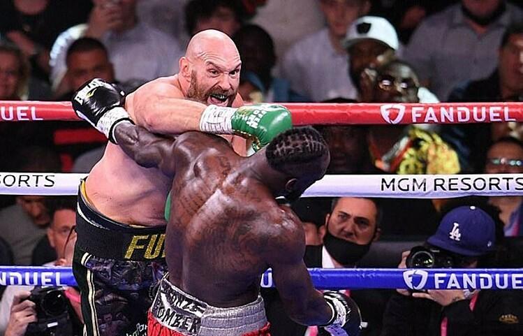 Fury tung cú đấm tay phải vào mặt Wilder, trong trận đánh ở Las Vegas. Ảnh: AFP.